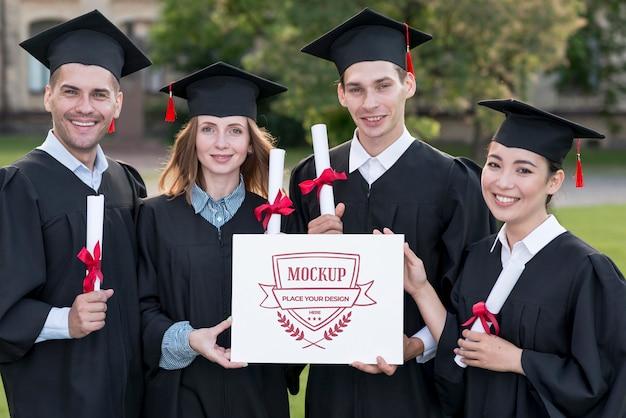 Graduados sosteniendo con orgullo un diploma de maqueta