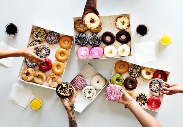 Groep die handen zoet doughnutdessert houden