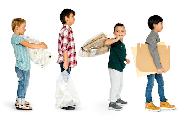 Groep kleine jongens die afval dragen om te recycleren
