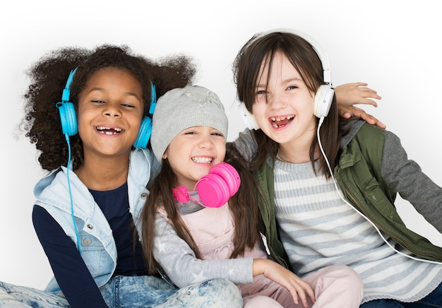 Groep meisjesstudio die dragend hoofdtelefoons en de winterkleren glimlachen