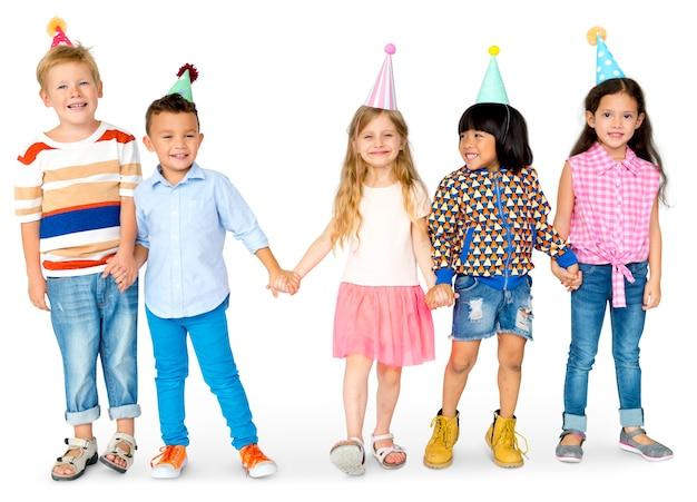 Groep van verschillende kinderen hand in hand in een feestmuts