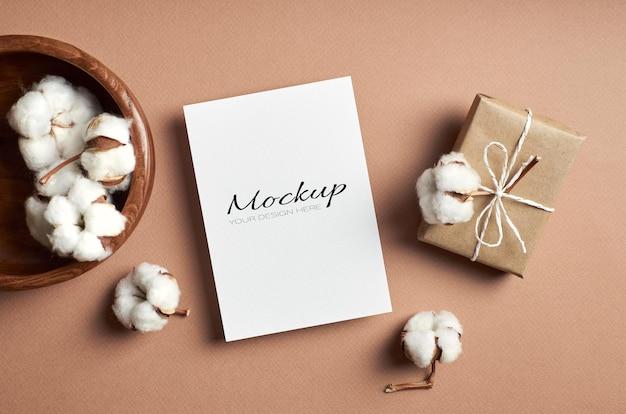 Groet- of uitnodigingskaartmodel met geschenkdoos en decoraties van katoenen bloemen