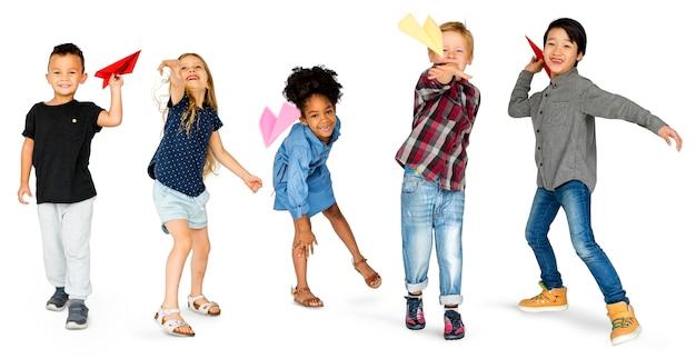 Grupo diverso de niños lanzando avión de papel