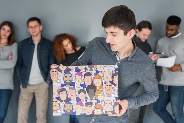Grupo de gente sujetando maqueta de cartel para caridad