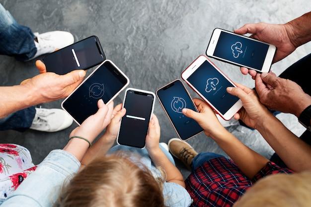 Grupo de personas mirando teléfonos inteligentes.