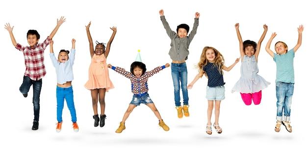 Gruppo vario di bambini che saltano e che si divertono