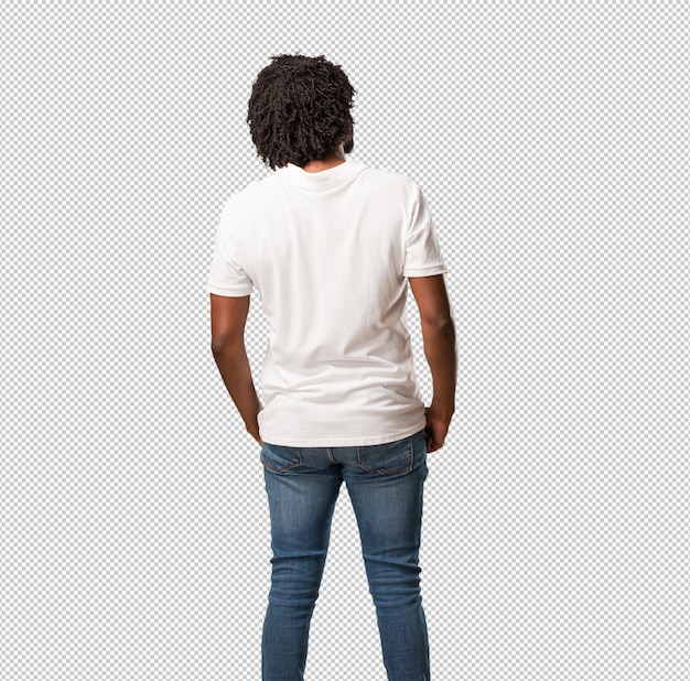 Guapo afroamericano mostrando atrás, posando y esperando, mirando hacia atrás