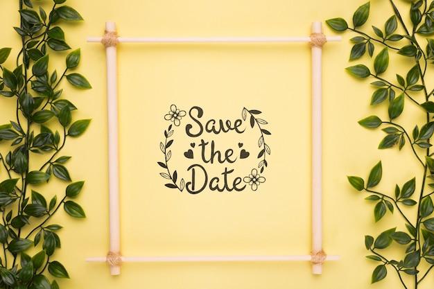 Guarde el marco de la maqueta de fecha con pequeñas ramas con hojas
