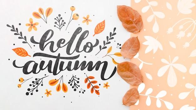 Hallo herfst belettering naast bruine bladeren patroon