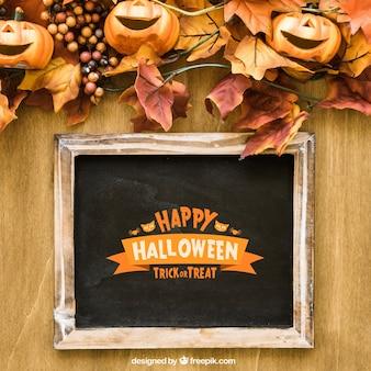 Halloween leisteen mockup met lachende pompoenen op de herfstbladeren