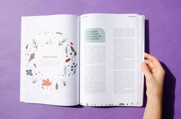 Hand die een tijdschrift op purpere achtergrond houdt