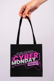 Hand met een cyber maandag papieren zak