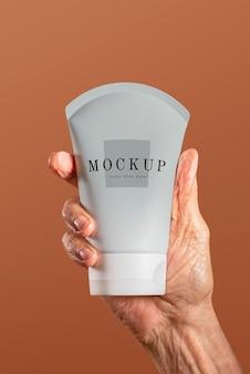 Hand met een mockup voor een gezichtscrèmebuiscontainer
