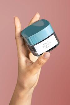 Hand met gezichtscrème pot mockup