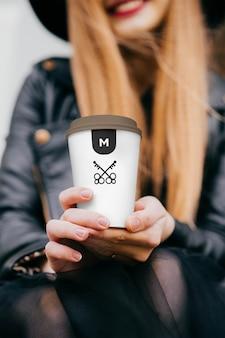 Hand met koffiekopje mockup