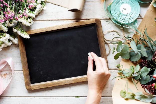 Hand met krijt en schrijven op leisteen