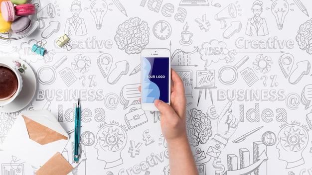 Hand met mobiel bureauconcept met hulpmiddelen