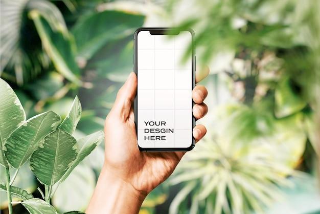 Hand met nieuw smartphonemodel omringd door bladeren