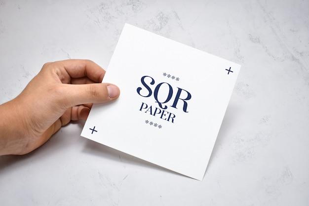 Hand met vierkante brochure mockup