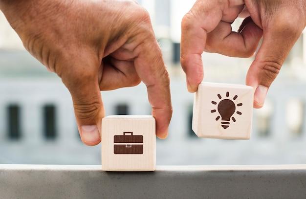 Handen die dobbelstenen met bedrijfideeën buitenshuis