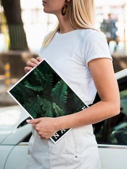 Handen die een natuurmagazine naast een auto houden