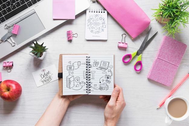 Handen die een notitieboekje op bedrijfsbureau houden