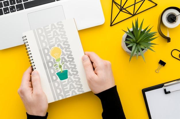 Handen die notitieboekjemodel over bureau houden