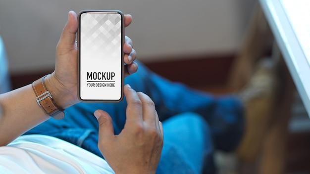 Handen met behulp van smartphonemodel op werktafel