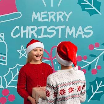 Hermanos jóvenes intercambian maqueta de regalos