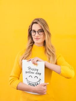 Hermosa mujer con maqueta de concepto amarillo
