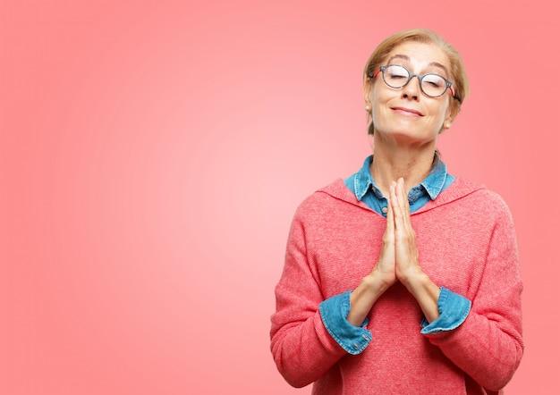 Hermosa mujer senior rezando de manera santa, mendigando