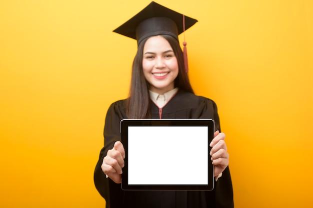 Hermosa mujer en toga de graduación tiene maqueta de tableta