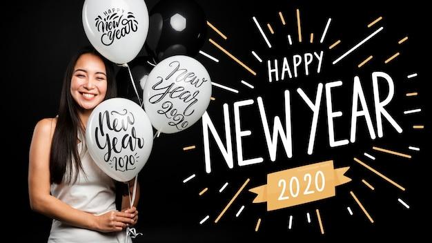 Hermosa niña sosteniendo globos feliz año nuevo 2020