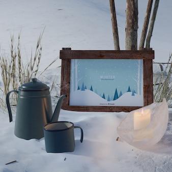 Hervidor de agua y taza junto al marco con tema de invierno