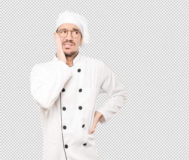 Het betrokken jonge chef-kok stellen tegen achtergrond