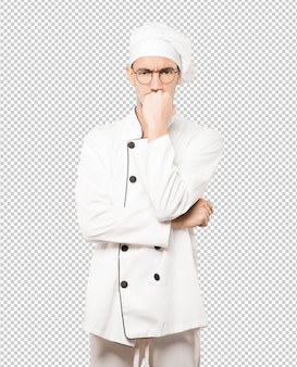 Het boze jonge chef-kok stellen tegen achtergrond