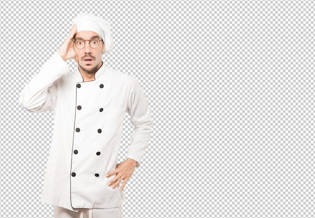 Het gedeprimeerde jonge chef-kok stellen tegen achtergrond