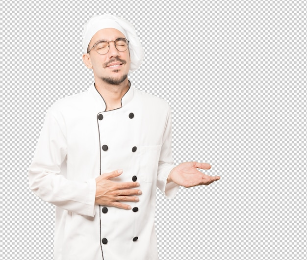 Het gelukkige jonge chef-kok denken aan voedsel