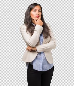Het jonge bedrijfs indische vrouw denken en het kijken omhoog, verward over een idee, zou een oplossing proberen te vinden