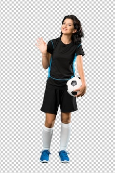 Het jonge voetbalstervrouw groeten met hand met gelukkige uitdrukking