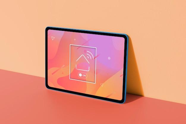 Het kleurrijke model van het digitale tabletscherm leunt op de muur