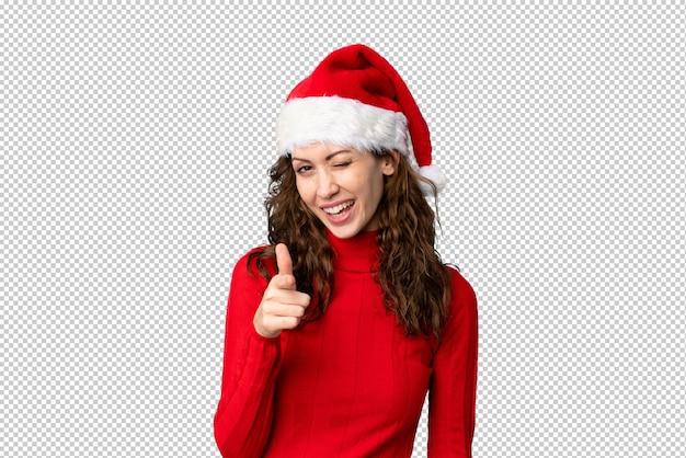 Het meisje met kerstmishoed richt vinger op u