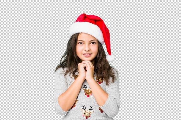 Het meisje viert kerstmisdag houdt handen onder kin, kijkt gelukkig opzij.