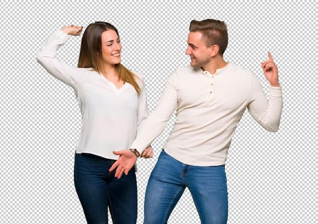 Het paar in valentijnskaartdag geniet van dansend terwijl het luisteren aan muziek op een partij