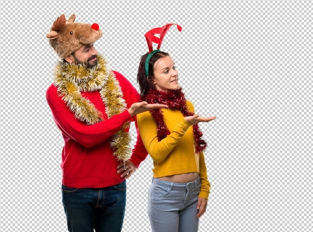 Het paar kleedde zich omhoog voor de kerstmisvakantie die een idee voorstellen terwijl het kijken naar het glimlachen