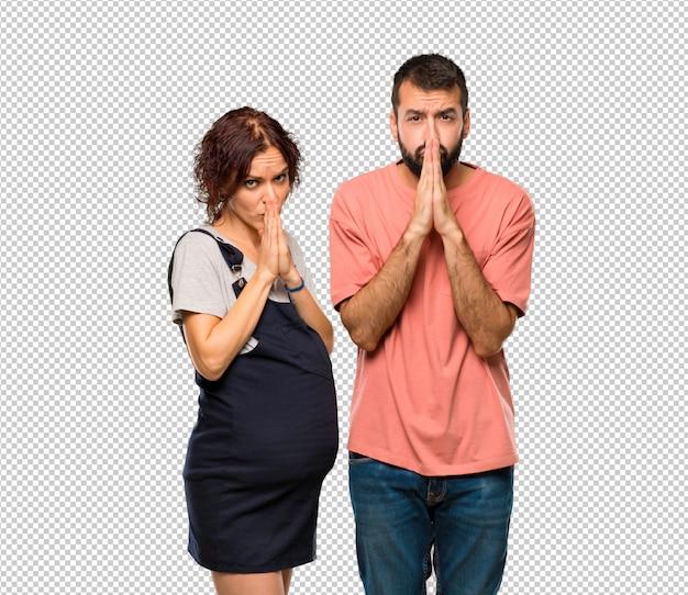 Het paar met zwangere vrouw houdt palm samen. persoon vraagt iets