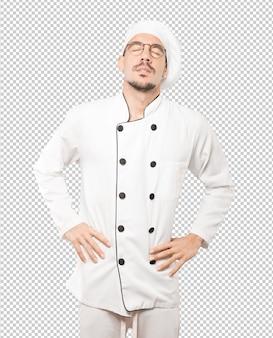 Het vermoeide jonge chef-kok stellen tegen achtergrond