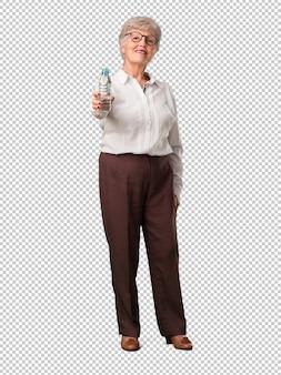 Het volledige lichaam hogere vrouw tevreden glimlachen, die een fles koud water houden