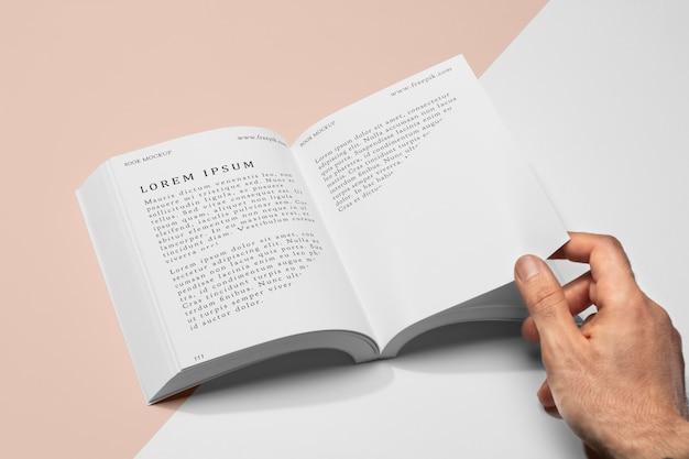 Hoge hoek hand met pagina van open boek mock-up