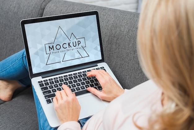 Hoge hoek van blonde vrouw die op laptop werkt